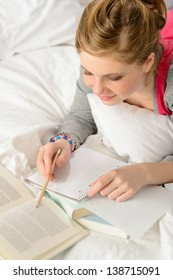 Teenage girl concentrating on studying from book lying on bed