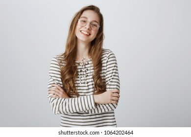 Teenage girl confident in herself. Portrait of good-looking young creative woman in transparent trendy eyewear standing with crossed hands on chest and smiling broadly, being smart and self-assured