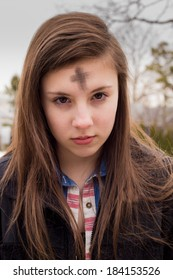 Teenage girl with cross on forehead in observance of Ash Wednesday
