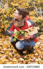 Teenage girl crouching outdoors among falling leaves, autumn