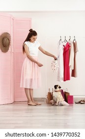Teenage girl with cute pug dog in dressing room