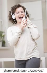 Teenage girl dancing to mp3 player, singing