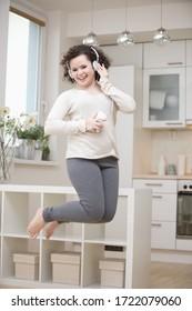 Teenage girl dancing to mp3 player, jumping