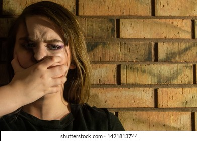 Teenage girl with dark hair and a hand over her mouth near a brick wall