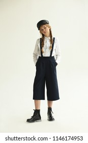 A teenage girl in dark trousers and a white blouse. Fashion & Style.