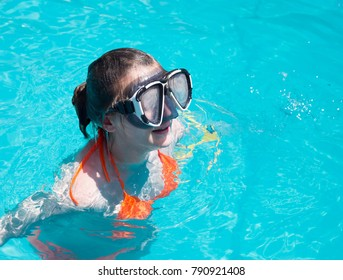 Teenage girl with diving goggles swimming in a pool