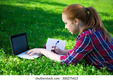 teenage girl doing her homework in summer park