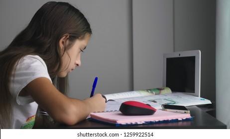 Teenage girl doing homework for school in her room, on the desk