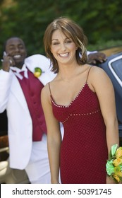 Teenage girl in dress outside limo with date behind, portrait