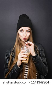 Teenage girl drinking takeaway coffee from a straw, wearing black outfit, against black background. No retouch, studio lighting.