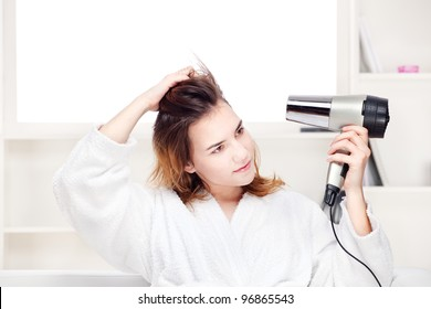 Teenage girl drying her hair at home