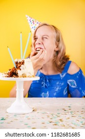 Teenage girl eating  birthday cake with her hands. One person party. Concept of birthday party, messthetics and misconduct. Vertical