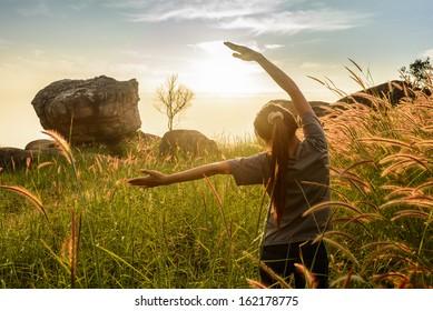 Teenage girl enjoy with sunshine in wheat field