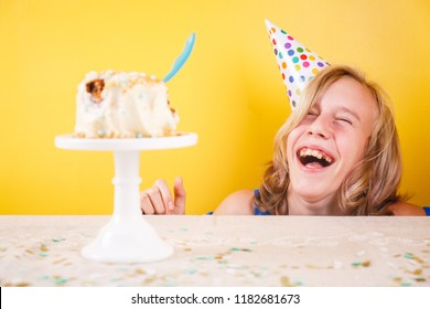 Teenage girl enjoying herself after ruining birthday cake. One person party. Concept of birthday party, messthetics and misconduct. Horizontal