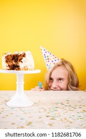 Teenage girl enjoying herself after ruining birthday cake. One person party. Concept of birthday party, messthetics and misconduct. Vertical