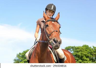 Teenage girl equestrian riding horseback. Vibrant summertime outdoors image.