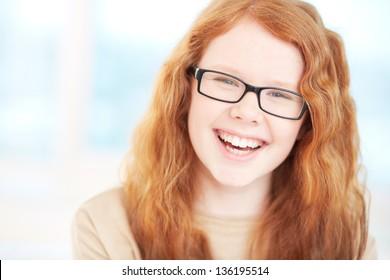 Teenage girl in eyeglasses looking at camera and laughing