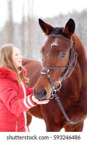 Teenage girl feeding bay horse on winter field. Friendship concept image