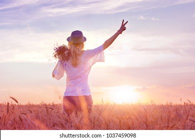 Teenage girl feels freedom and relaxing outdoors, enjoying nature with the sunrise field of wheat. The concept of freedom and happiness. Landscape background, copy space.