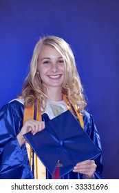 A teenage girl female graduating from high school isolated against a blue background.