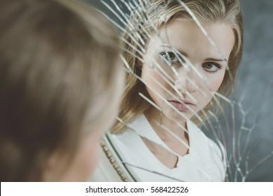 Teenage girl full of complexes looking at herself in the broken mirror