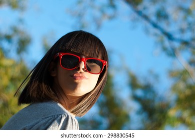 Teenage girl gives a kiss wearing red sunglasses under the trees. Picture taken from low
