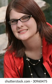 Teenage girl with glasses smiling by a rocky stream