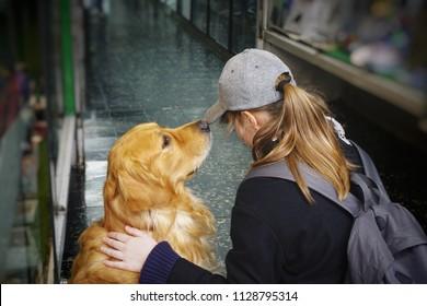 Teenage girl and a golden retriever on a city street