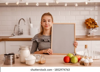 teenage girl in a gray dress is going to cook a traditional apple pie in the new kitchen and holds an empty wooden rack with a gray background with a place for text..