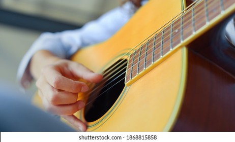 Teenage girl hand playing guitar. Female musician learning to play guitar. Closeup young woman practicing music on string instrument. Unrecognizable guitarist fingers strumming strings of guitar