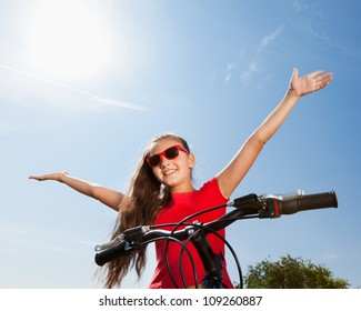 teenage girl with hands up on a bicycle