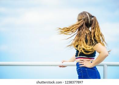 Teenage girl having brown ponytails windblown tousled hair. Unrecognizable woman having outdoor fun.