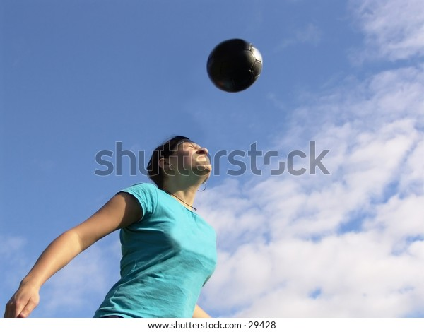Teenage girl heading a soccerball. Funny expression.