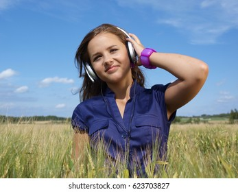 teenage girl with headphones in a field listening music