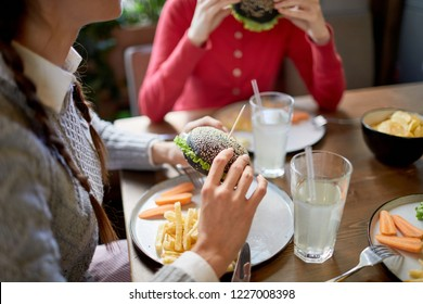 Teenage girl and her friend having cheeseburgers and french fries for lunch in fast food cafe