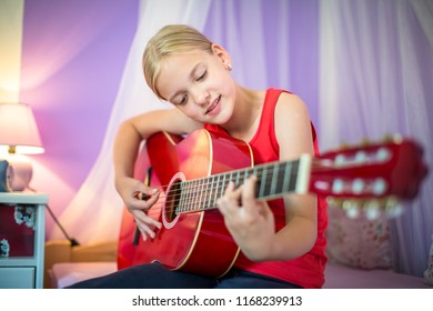 Teenage girl with her guitar in her lovely room