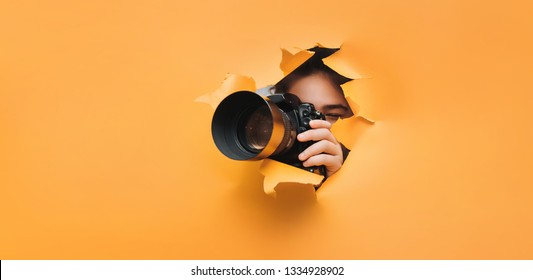 A teenage girl is holding a black camera with a telephoto lens that looks out through a torn hole in yellow paper. Concept of paparazzi, espionage, yellow press.