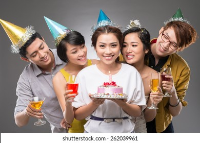 Teenage girl holding a cake with her friends behind