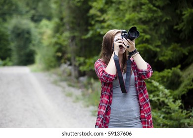 Teenage girl holding a camera shooting apicture outdoors