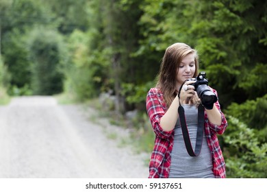 Teenage girl holding a camera shooting a picture outdoors. She is looking at the back of the camera