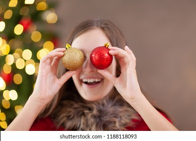 teenage girl holding  christmas balls in front of her eyes and smiling, christmas tree in background
