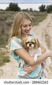 Teenage girl holding dog walking on a dirt road in a rural area, with an instagram or vintage filter