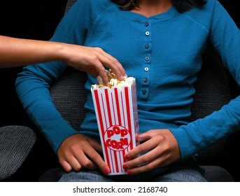 Teenage girl holding a popcorn bucket at the movies with a friend reaching into bucket for a handful.