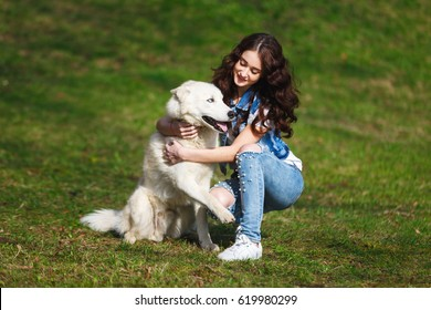 Teenage girl is hugging two husky dogs in a park