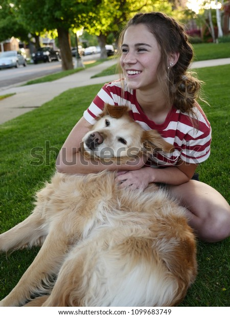 A teenage girl hugs her Golden Retriever and smiles while sitting in the front yard of a house on the lawn.