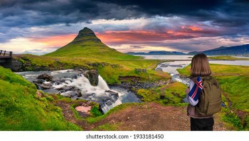 Teenage girl with Icelandic flag in backpack traveling in Iceland. Fantastic sunrise on famous Kirkjufellsfoss Waterfall with Kirkjufell peak on background. Snaefellsnes peninsula, Iceland, Europe