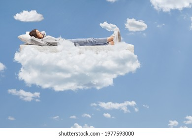 Teenage girl in jeans and hoodie resting on a mattress on clouds up in the sky