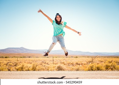 Teenage girl jumping on open road in summer