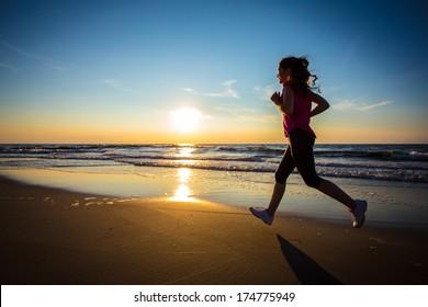 Teenage girl jumping, running on beach