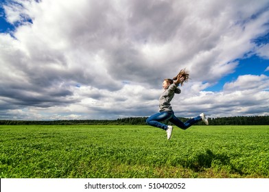 teenage girl jumping in summer field
